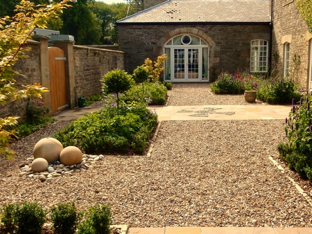 A large traditional stone courtyard garden designed with enclosing gravel paths, formal parterre beds and a stone sphere water feature. Click image for more details.