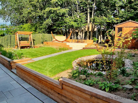 A terraced rear garden with a Siberian larch retaining wall the full width of the garden. Above the wall, to the right, lies a Japanese maple tree, a cobble-bordered wildlife pond and a bespoke wooden shed. To the right are meadow borders, a swing seat and a large deck. Click image for more details.