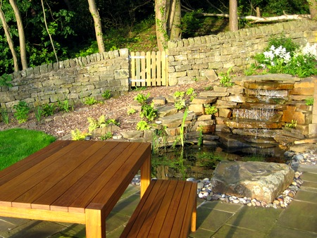A cedar table & bench seat are placed in front of a natural stone waterfall. Behind is a bark path and low stone wall with a wooden gate leading to the woodland to the rear. Click image for more details.