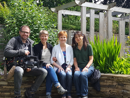 Image of Sophia and Julie and the film crew for 'Love Your Garden' sat on the curved stone seat