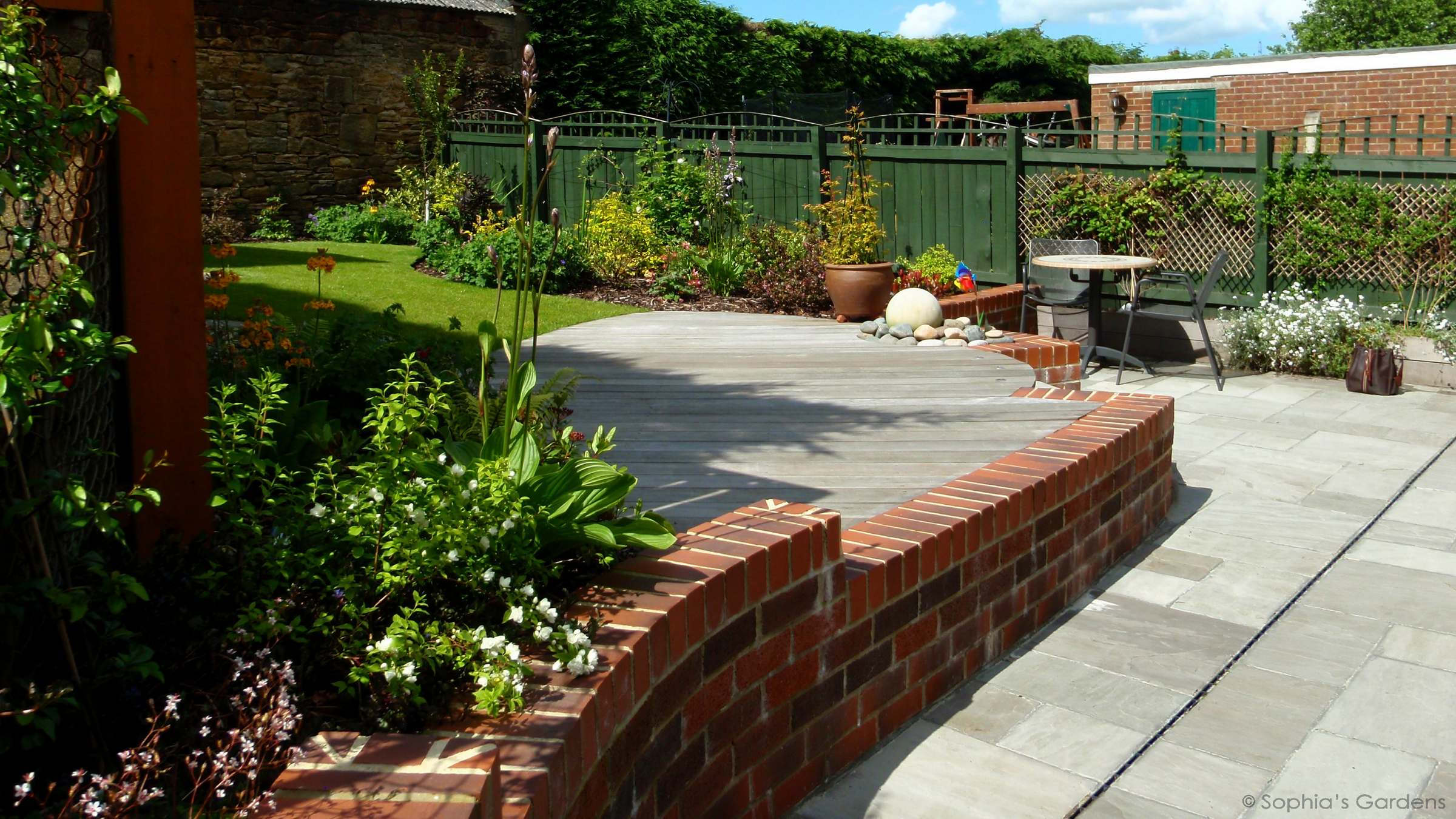 Curvaceous brick wall, hardwood deck and water features. Low-maintenance design in Lanchester, by Sophia's Gardens